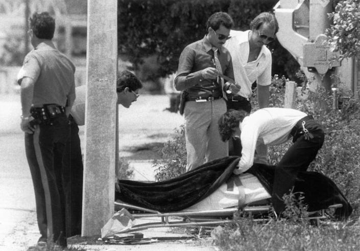 The body of Carl R, Brown is removed by police he left eight men and women dead and three others wounded at Bob Moore's Welding and Machine Service, 3147 NW North River Dr. during a shooting rampage in August of 1982. Brown was killed when an outraged motorist who knew the victims deliberately crushed him against a concrete light pole with his car. Brown killed owner Bob Moore's mother, Ernestine Moore, 67; his uncle, Mangum Moore, 78, the bookkeeper; Carl Lee, 47, the manager