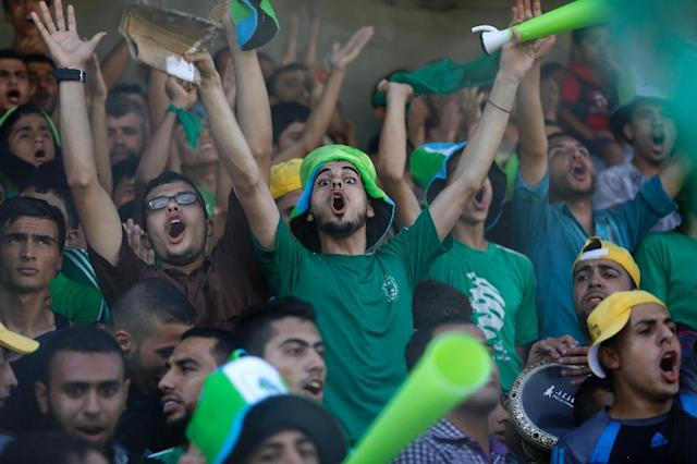 Palestinian spectators cheer during a football match between the West Bank-based Al-Ahli and Gaza's Shejaiya at the al-Yarmuk stadium in Gaza City on August 6, 2015 (AFP Photo/Mohammed Abed)