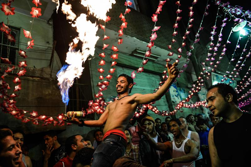 In this Tuesday, April 16, 2013 photo, a shirtless Egyptian man dances with fire during a wedding party in Cairo, Egypt. Egypt's economy has been hard hit by the two years of turmoil that followed the ouster of longtime President Hosni Mubarak. Half of the country's 85 million people live at or below the poverty line of $2 a day and rely on government subsidies of wheat and fuel for survival.(AP Photo/Eman Helal)