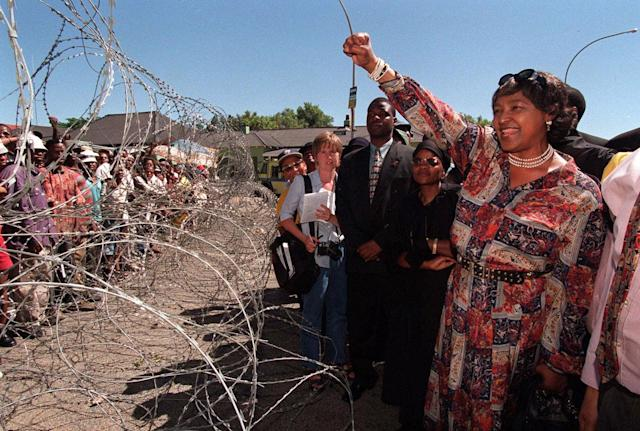 <p>Winnie Madikizela-Mandela, former wife of Nelson Mandela, greets demonstrators behind razor wire at a bail hearing for businessman Piet Odendaal in Viljoenskroon, in the Orange Free State, South Africa, Nov. 10, 2000. Odendaal was accused of murdering a black employee and dragging his body behind a truck in the nearby town of Sasolburg. (Photo: Lori Waselchuk/AP) </p>
