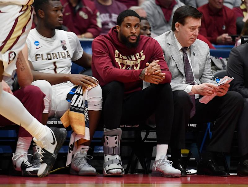 Florida State's Phil Cofer (0) sits on the bench with a boot on his right foot during the second half of a first round men's college basketball game against Vermont in the NCAA tournament, Thursday, March 21, 2019, in Hartford, Conn. (AP Photo/Jessica Hill)