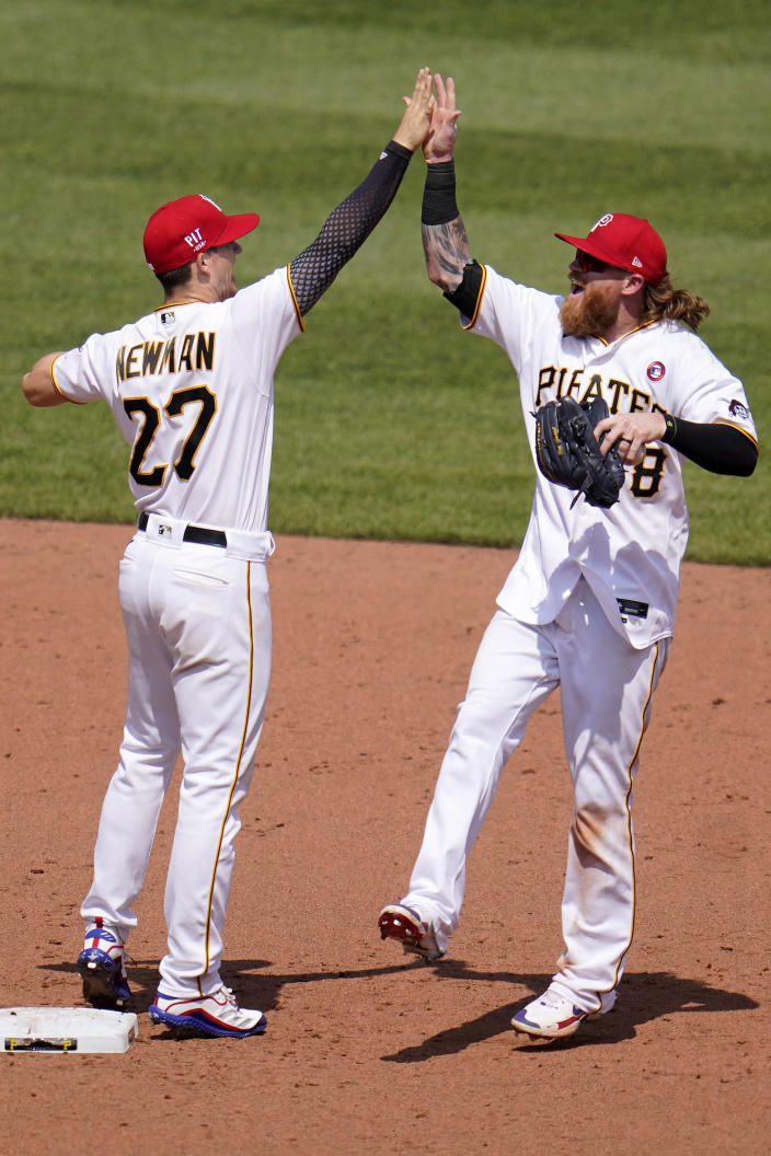 Pittsburgh Pirates' Kevin Newman (27) and Ben Gamel celebrates after getting the final out for a win over the Milwaukee Brewers in a baseball game in Pittsburgh, Sunday, July 4, 2021. (AP Photo/Gene J. Puskar)