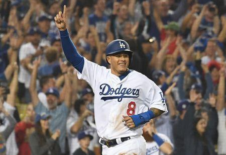 FILE PHOTO: Oct 27, 2018; Los Angeles, CA, USA; Los Angeles Dodgers shortstop Manny Machado (8) celebrates after scoring on a three run home run hit by outfielder Yasiel Puig (66) in the sixth inning against the Boston Red Sox in game four of the 2018 World Series at Dodger Stadium. Mandatory Credit: Richard Mackson-USA TODAY Sports