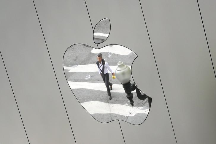 FILE PHOTO: A man is reflected in a Apple store logo in San Francisco