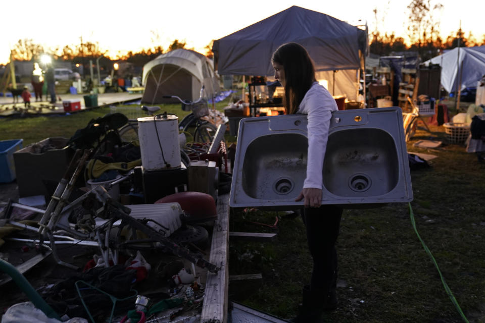 Cristin Trahan carries a sink to wash her dishes, amidst the rubble of the family's destroyed home in Lake Charles, La., Friday, Dec. 4, 2020. They were hit by Hurricanes Laura and Delta. She, her husband and a son are living in tents on the property, while her other son, his fiancée and their one-year old son are living in a loaned camper there. A relative's home on the same property is now gutted and they are living in a camper as well. (AP Photo/Gerald Herbert)