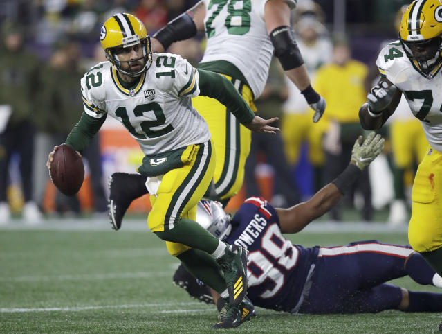 Green Bay Packers quarterback Aaron Rodgers (12) scrambles away from New England Patriots defensive end Trey Flowers (98) during the first half of an NFL football game, Sunday, Nov. 4, 2018, in Foxborough, Mass. (AP Photo/Charles Krupa)