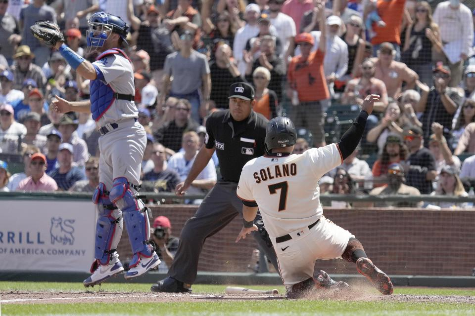 San Francisco Giants' Donovan Solano, right, slides into home plate past Los Angeles Dodgers catcher Austin Barnes, left, to score a run on a double by LaMonte Wade Jr. during the seventh inning of a baseball game Thursday, July 29, 2021, in San Francisco. (AP Photo/Tony Avelar)