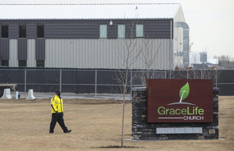 A security officer walks beside the sign at the entrance to GraceLife Church. The grey church building is behind him.