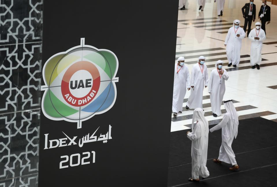 Visitors and officials arrive for the opening day of the International Defence Exhibition & Conference, IDEX, in Abu Dhabi, United Arab Emirates, Sunday, Feb. 21, 2021. (AP Photo/Kamran Jebreili)