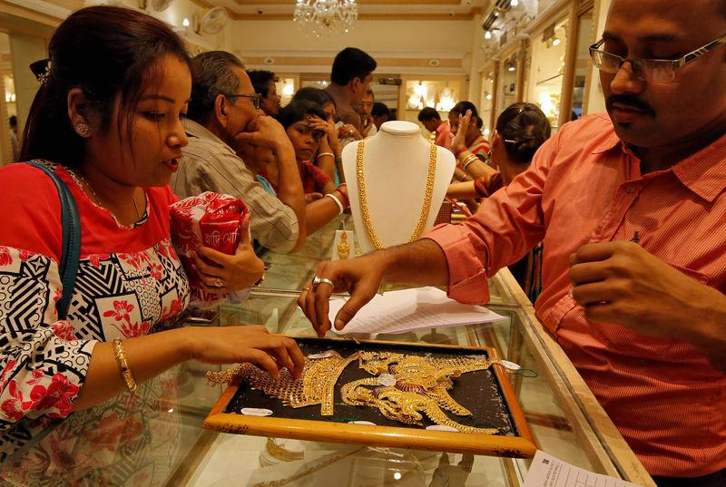 FILE PHOTO: A salesman shows gold necklaces to a customer at a jewellery showroom in Kolkata