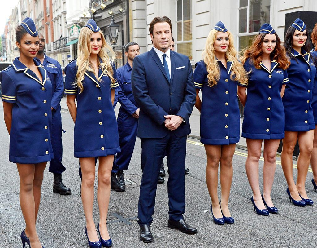 John Travolta is a licensed pilot and aviation fanatic, so it was fitting that the TK-year-old was front and center (and surrounded by flight attendants!) on Thursday for the launch of the Manhattan flaghship store of Breitling, which makes high-end watches for pilots. (6/27/2013)