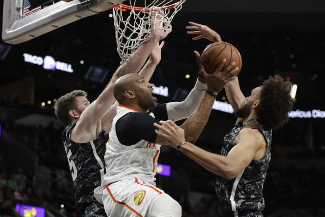 Atlanta Hawks guard Vince Carter, center, drives to the basket between San Antonio Spurs defenders Jakob Poeltl, left, and Derrick White, right, during the first half of an NBA basketball game in San Antonio, Friday, Jan. 17, 2020. (AP Photo/Eric Gay)