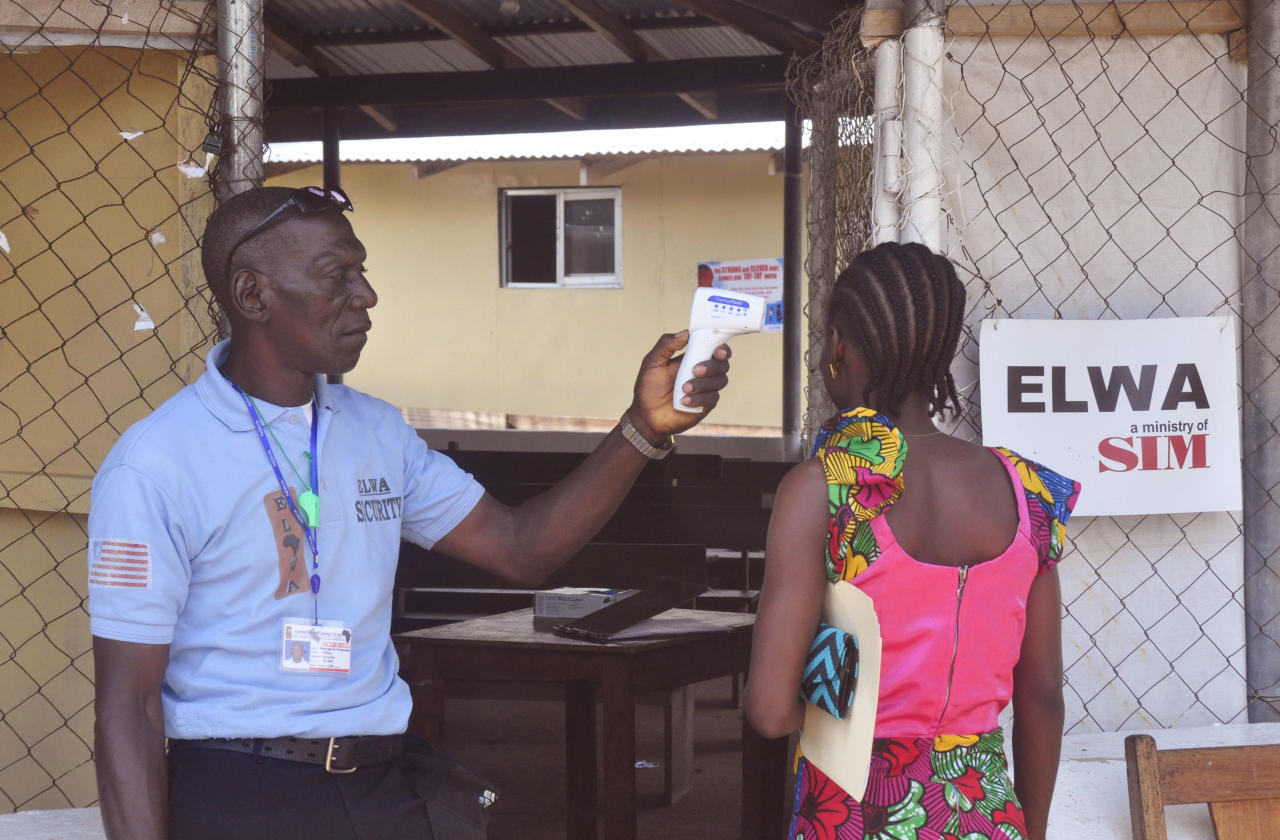 A unidentified family member, right, of a 10-year old boy that contracted Ebola, has her temperature measured by a health worker before entering the Ebola clinic were the child is being treated on the outskirts of Monrovia, Liberia, Friday, Nov. 20, 2015. Health authorities are reporting one confirmed Ebola case, a 10-year boy who is currently being attended to at the treatment center on the outskirts of Monrovia, the capital.(AP Photo/ Abbas Dulleh)