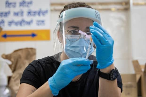 Switch Health nurse Samantha Edgar prepares a does of the Pfizer-BioNTech COVID-19 vaccine at a clinic in Mississauga earlier this month. (Evan Mitsui/CBC - image credit)