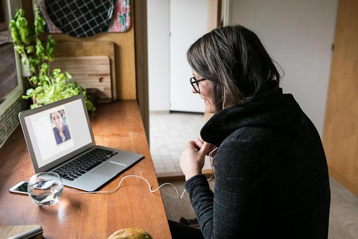 Side view of businesswoman video calling female colleague on laptop in home office (Getty Images)
