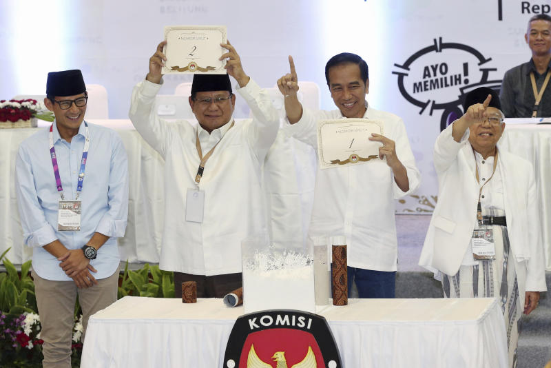 FILE - In this Sept. 21, 2018, file photo, Indonesian presidential candidates Prabowo Subianto, second from left, and his running mate Sandiaga Uno, left, Joko Widodo, second from right, and his running mate Ma'ruf Amin, show the ballot numbers that will represent them in the upcoming presidential election, during a draw at the General Election Commission office in Jakarta, Indonesia. Indonesia's presidential election Wednesday, April 17, 2019 is a re-run of the 2014 contest when Widodo, a furniture business owner who became Jakarta governor, vied with the former special forces general to lead the world's third-largest democracy and most populous Muslim-majority nation. (AP Photo/Achmad Ibrahim, File)