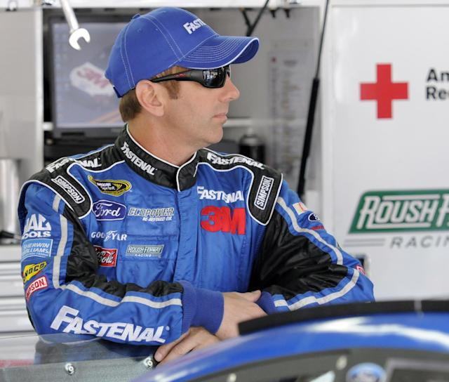 Greg Biffle waits by his car before practice for Sunday's NASCAR Sprint Cup series Coca-Cola 600 auto race at Charlotte Motor Speedway in Concord, N.C., Thursday, May 22, 2014. (AP Photo/Mike McCarn)