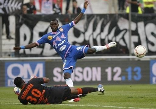 Evian's Ghanaian midfielder Mohammed Rabiu, right, challenges Marseille's French goalkeeper Steve Mandanda for the ball during their League One soccer match, at the Velodrome stadium, in Marseille, southern France, Sunday, Sept. 23, 2012. (AP Photo/Claude Paris)