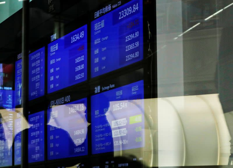 People are reflected on a glass in front of a large screen showing stock prices at the Tokyo Stock Exchange after market opens in Tokyo