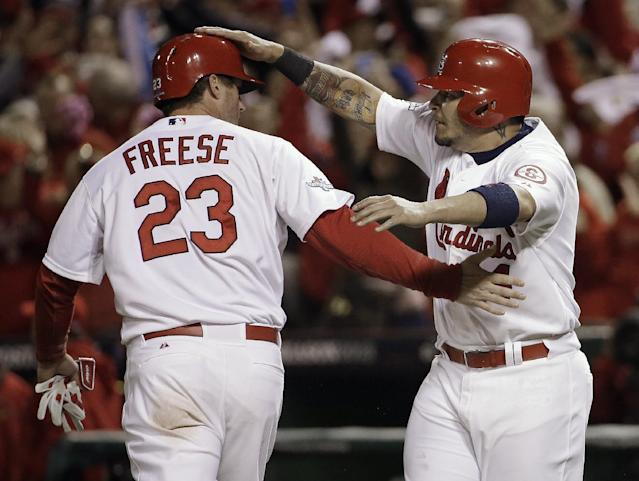 St. Louis Cardinals' David Freese and Yadier Molina celebrate after both scored on a hit by Shane Robinson during the third inning of Game 6 of the National League baseball championship series against the Los Angeles Dodgers, Friday, Oct. 18, 2013, in St. Louis. (AP Photo/David J. Phillip)