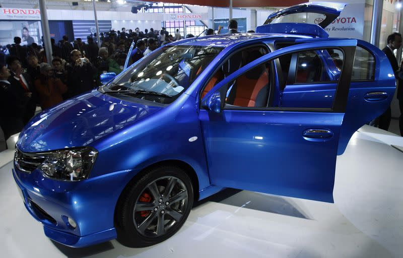 File photo of onlookers standing next to Toyota's Etios compact car in New Delhi