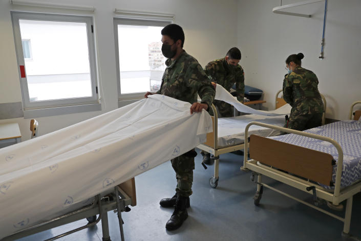 Soldiers prepare beds in a new COVID-19 ward being set up at the Military Hospital in Lisbon, Tuesday, Jan. 26, 2021. The military hospital is expanding it's number of beds available to take COVID-19 patients from the National Health Service. Portugal is reporting new daily records of COVID-19 deaths and hospitalizations as a recent pandemic surge continues unabated. (AP Photo/Armando Franca)