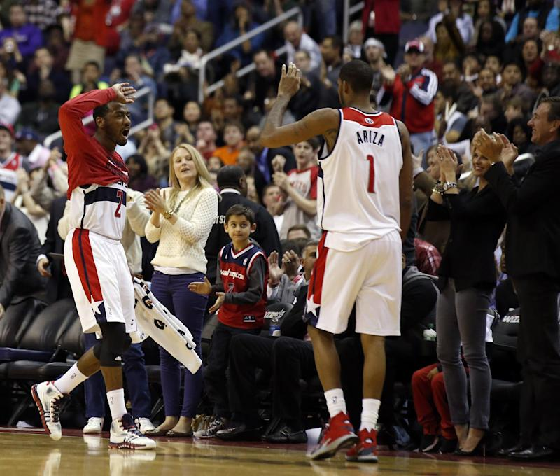 Washington Wizards guard John Wall (2) celebrates with forward Trevor Ariza (1) in the second half of an NBA basketball game against the Oklahoma City Thunder, Saturday, Feb. 1, 2014, in Washington. The Wizards won 96-81. (AP Photo/Alex Brandon)