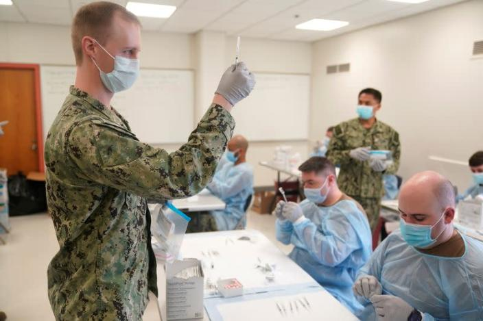 Navy personnel prepare doses of the COVID-19 vaccine before the opening of a mass vaccination site in the Queens borough of New York