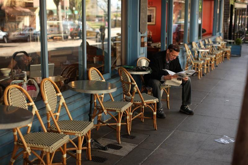 A man reads a newspaper at a sidewalk cafe in the North Beach neighborhood in San Francisco, California.