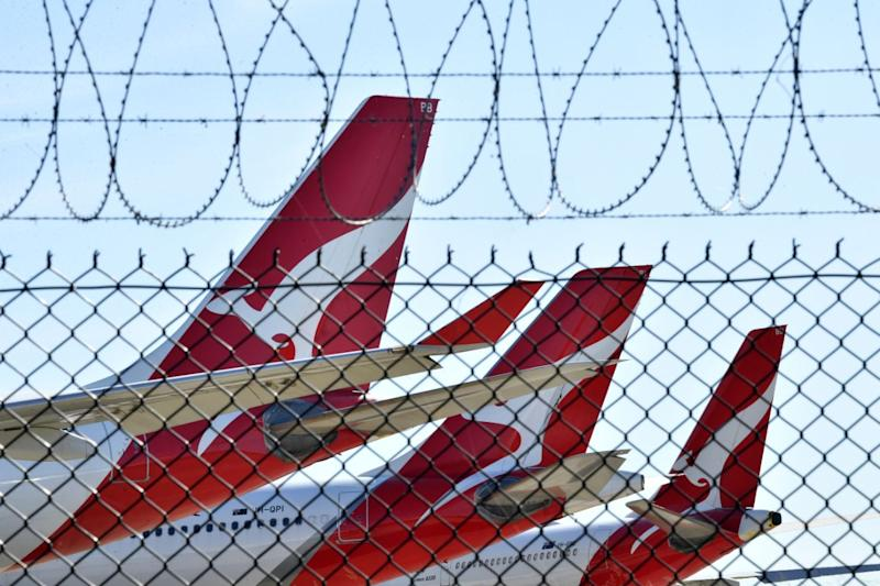 A photo of Qantas planes through a barbed wire fence.