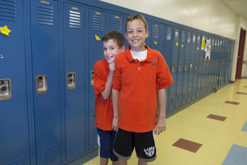 In this Thursday, June 6, 2013 photo, Ryan Novosel, left, and his twin brother, Luke, one of the twenty-four sets of twins from Highcrest Middle School in Wilmette, Ill., pose for a portrait at the school. The group is attempting to break a Guinness World record for the amount of twins in one grade which is currently 16 sets. (AP Photo/Scott Eisen)
