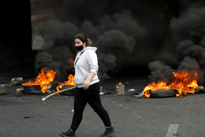 A protester passes in front of burned tires as she blocks a main highway, during a protest in the town of Zouk Mosbeh, north of Beirut, Lebanon, Monday, March 8, 2021. The dayslong protests intensified Monday amid a crash in the local currency, increase of consumer goods prices and political bickering between rival groups that has delayed the formation of a new government. (AP Photo/Hussein Malla)