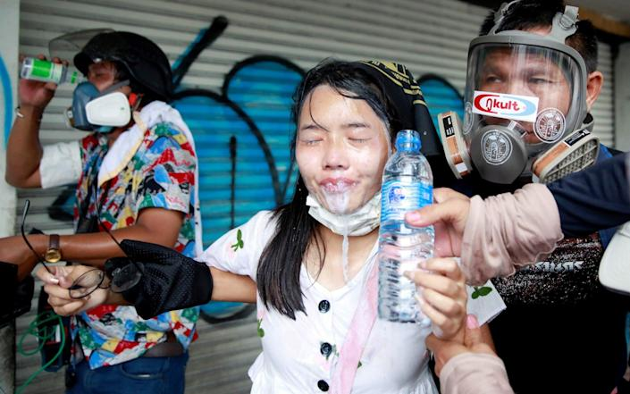 A demonstrator gets assistance during a protest against the Thai government's handling of the pandemic in Bangkok, Thailand on 13 August 2021 - Soe Zeya Tun/Reuters