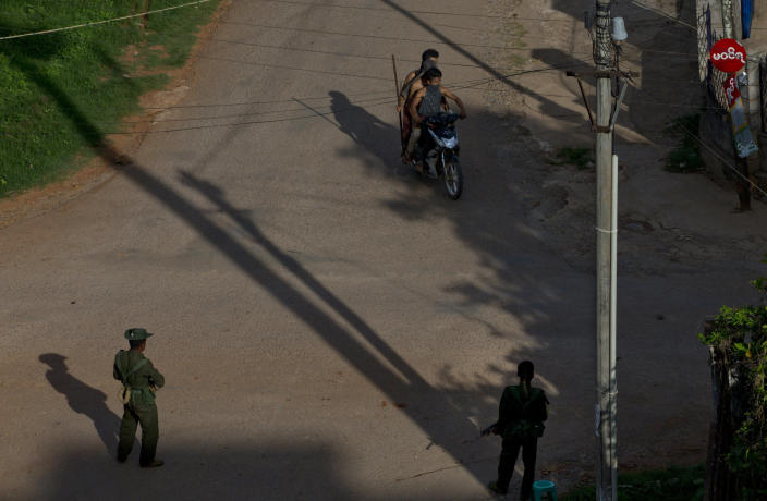 Buddhists on a motorcycle armed with sticks patrol in the streets as armed army officers watch in Lashio, northern Shan State, Myanmar, Wednesday, May 29, 2013. Hundreds of Buddhist men on motorcycles waved iron rods and bamboo poles and threw rocks in the northeastern Myanmar town on Wednesday, a day after a mosque and a Muslim orphanage were torched in a new wave of violence targeting the religious minority. (AP Photo/Gemunu Amarasinghe)