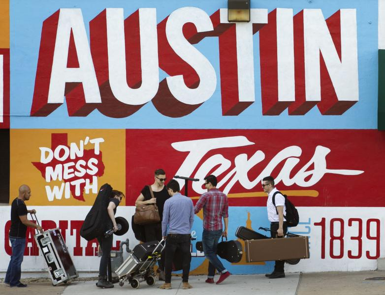 FILE - In this March 14, 2013 file photo, a band is on the move on the corner of Sixth Street and I-35 at South by Southwest in Austin, Texas. iTunes is putting its stamp on South by Southwest, piggybacking on the annual event hosted by the city of Austin, Texas, with its own music festival. The company said Wednesday, Feb. 19, 2014, it will debut its popular iTunes Festival, a free concert series held in London for the past seven years. While the London version is a 30-day event, the U.S. festival will feature five nights of rock, country, pop and hip-hop held at the ACL Live at the Moody Theater, where Austin City Limits is held. (AP Photo/Austin American-Statesman, Jay Janner) AUSTIN CHRONICLE OUT, COMMUNITY IMPACT OUT, MAGS OUT; NO SALES; INTERNET AND TV MUST CREDIT PHOTOGRAPHER AND STATESMAN.COM