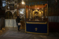 Christian worshipper prays in the Church of the Nativity, traditionally believed to be the birthplace of Jesus Christ, in the West Bank city of Bethlehem, Monday, Nov. 23, 2020. Normally packed with tourists from around the world at this time of year, Bethlehem resembles a ghost town – with hotels, restaurants and souvenir shops shuttered by the pandemic. (AP Photo/Majdi Mohammed)