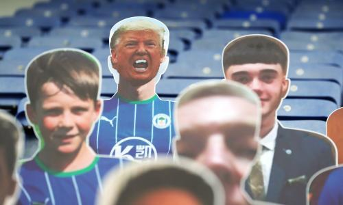 """Wigan v Stoke City - Sky Bet Championship - DW Stadium<br>A cardboard cutout of Donald Trump (top row, left) in the stands before the Sky Bet Championship match at the DW Stadium, Wigan. PA Photo. Issue date: Tuesday June 30, 2020. See PA story SOCCER Wigan. Photo credit should read: Martin Rickett/PA Wire. RESTRICTIONS: EDITORIAL USE ONLY No use with unauthorised audio, video, data, fixture lists, club/league logos or """"live"""" services. Online in-match use limited to 120 images, no video emulation. No use in betting, games or single club/league/player publications."""