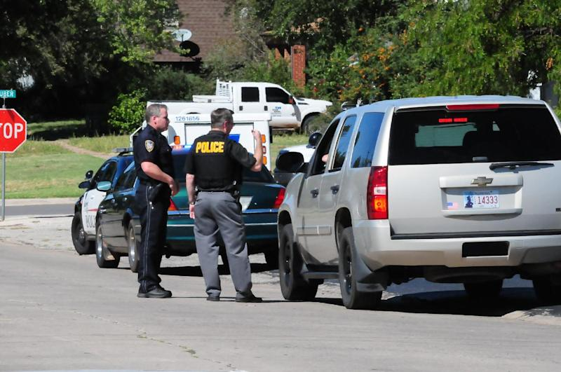 Weatherford Police direct cars away from schools as they tell parents the schools were on lock down Tuesday afternoon, Sept. 24, 2013, in Weatherford, Okla. The schools were on lockdown because eight inmates being transported by a private prison company escaped in their transport van. (AP Photo/Weatherford, Daily News)
