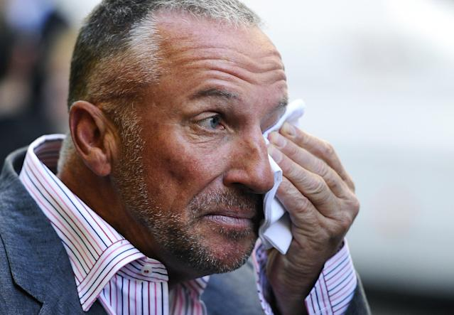 "Former cricket player Sir Ian Botham OBE (R) wipes his eye as he arrives for the world premiere of cricket film ""From the Ashes"", in London on May 10, 2011. AFP PHOTO/Carl de Souza. (Photo credit should read CARL DE SOUZA/AFP/Getty Images)"