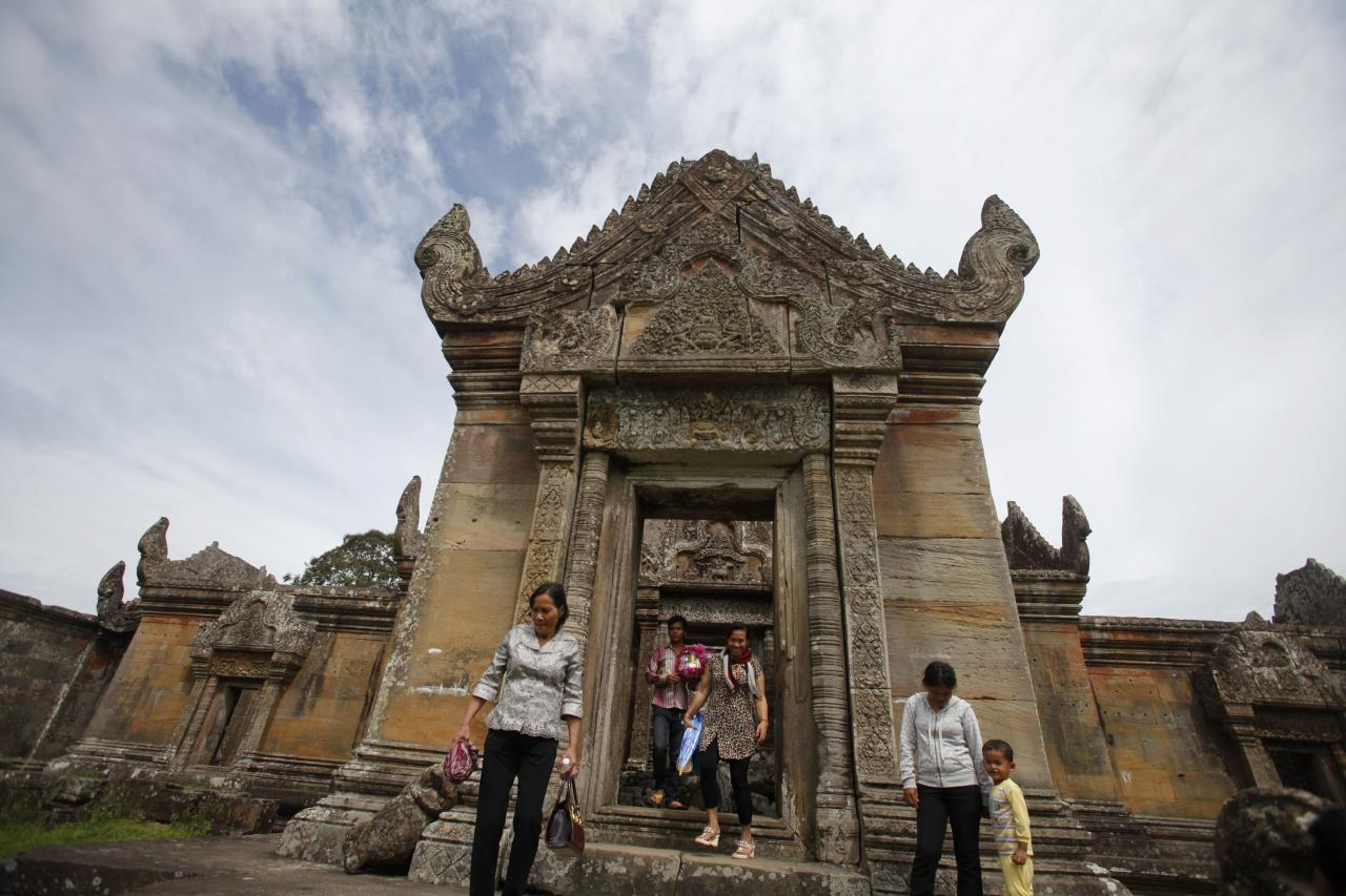 People visit the 900-year-old Preah Vihear temple on the border between Thailand and Cambodia November 10, 2013. The International Court of Justice (ICJ) will on November 11 give its verdict on a turf dispute concerning the 4.6-square-kilometre (1.8 sq mile) plot of scrub surrounding Preah Vihear. The ICJ awarded the temple to Cambodia in 1962, but did not clarify jurisdiction of the land around it. Periodic armed clashes along the border have resulted in deaths on both sides, and displaced tens of thousands of people from both countries over the years. REUTERS/Samrang Pring (CAMBODIA - Tags: CIVIL UNREST POLITICS RELIGION)