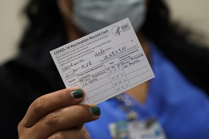 Nurse Helen Cordova shows her vaccination record card after receiving the Pfizer-BioNTech COVID-19 vaccine at Kaiser Permanente Los Angeles Medical Center in Los Angeles, Monday, Dec. 14, 2020. (AP Photo/Jae C. Hong)