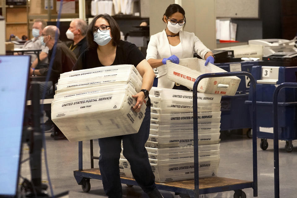 Arizona elections officials carry ballots in trays to be counted inside the Maricopa County Recorder's Office, Friday, Nov. 6, 2020, in Phoenix. (AP Photo/Matt York)