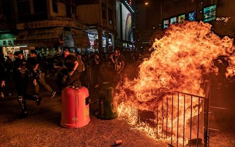 Pro-democracy protesters run behind a burning barricade after police charged toward them during a demonstration in Mongkok district - Credit: Getty