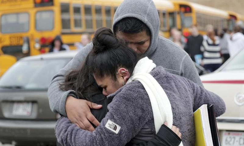 Becky Galvan, center, consoles her daughter, Ashley Galvan, with her father, Jose Chavez, outside Waukesha South high school on Monday.