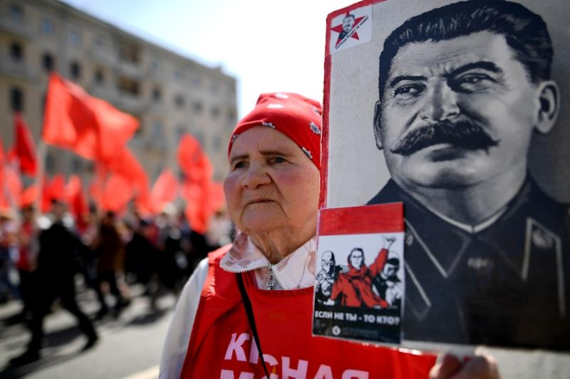 A Russian Communist party activist carries a portrait of late Soviet leader Joseph Stalin during a May Day rally in Moscow on May 1, 2017
