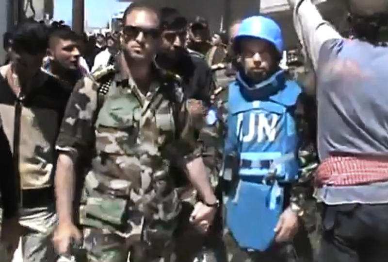 This image made from amateur video released by the Shaam News Network and accessed Sunday, April 22, 2012, purports to show a Free Syrian Army solider accompanying a UN observer in Rastan town in Homs, Syria. U.N. cease-fire monitors toured a rebel-held town in central Syria Sunday with army defectors, while government troops pounded a Damascus suburb with artillery and heavy machine guns, activists said. (AP Photo/Shaam News Network via AP video) TV OUT, THE ASSOCIATED PRESS CANNOT INDEPENDENTLY VERIFY THE CONTENT, DATE, LOCATION OR AUTHENTICITY OF THIS MATERIAL