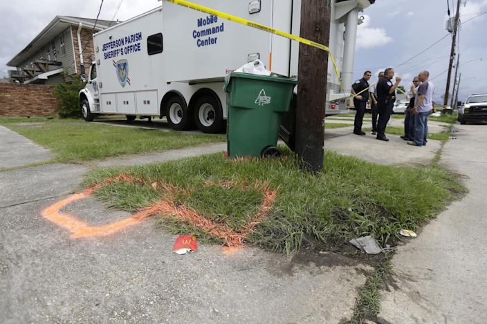 Police stand near spray paint markings of trash bins, where the body of missing 6-year-old Ahlittia North was found in Harvey, La., Tuesday, July 16, 2013, according to Lisa North, the child's mother. North says Jefferson Parish authorities told her they have found the body of her daughter in a Harvey trash bin. Ahlittia disappeared from her apartment late Friday night or early Saturday morning. North's husband Albert Hill said they were told the body was found in a trash bin not far from their apartment. (AP Photo/Gerald Herbert)