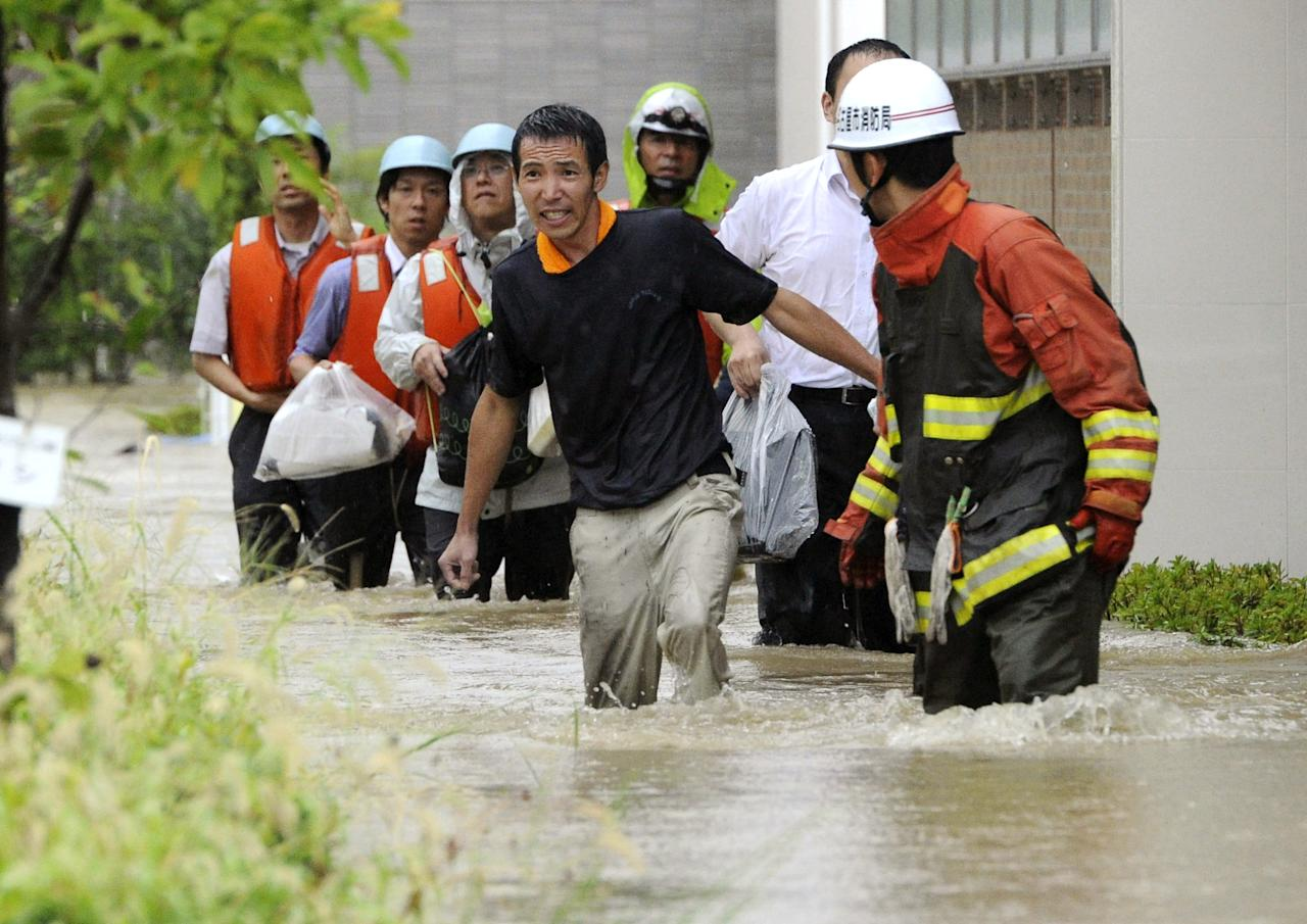 Local residents wade through a flooded street caused by approaching typhoon in Nagoya, central Japan, Tuesday, Sept. 20, 2011. Thousands of people in central Japan have been advised to evacuate as the powerful typhoon approaches. The storm system has already triggered floods that have left two people missing. (AP Photo/Kyodo News) JAPAN OUT, MANDATORY CREDIT, NO LICENSING IN CHINA, FRANCE, HONG KONG, JAPAN AND SOUTH KOREA