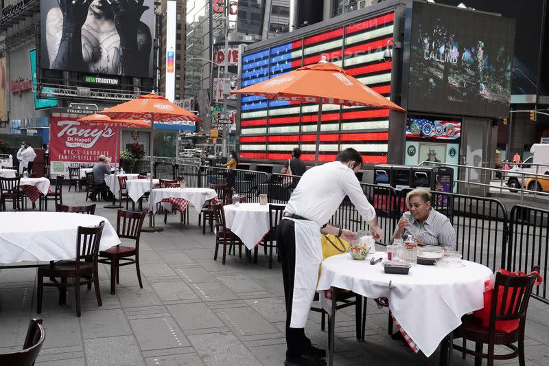 FILE PHOTO: Servers package food at a table at a pop up restaurant set up in Times Square in New York