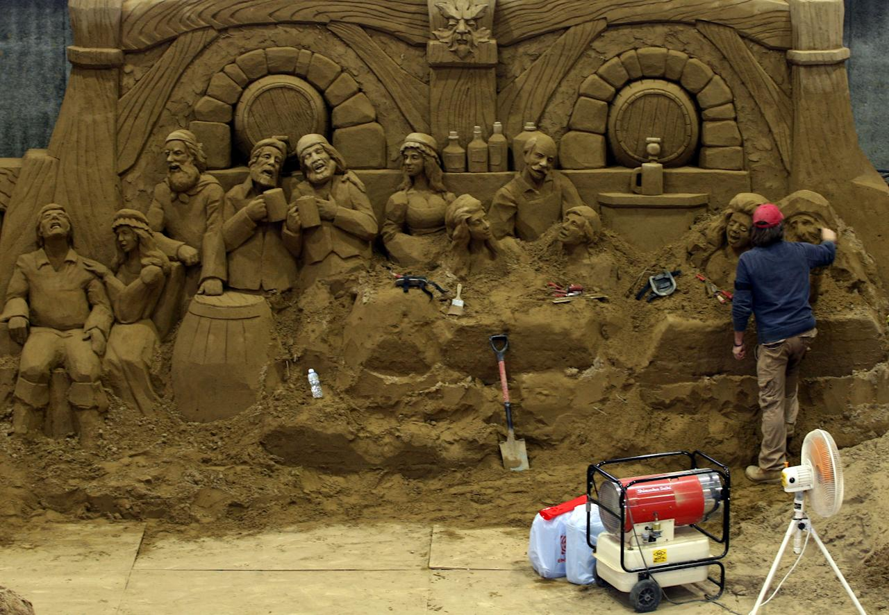 Daniel Belcher of the U.S. finishes a sand replica titled 'Traditional England Pub Laughter and Lively People' at Sand Museum located in the Tottori Dune on April 1, 2012 in Tottori, Japan. (Photo by Buddhika Weerasinghe/Getty Images)